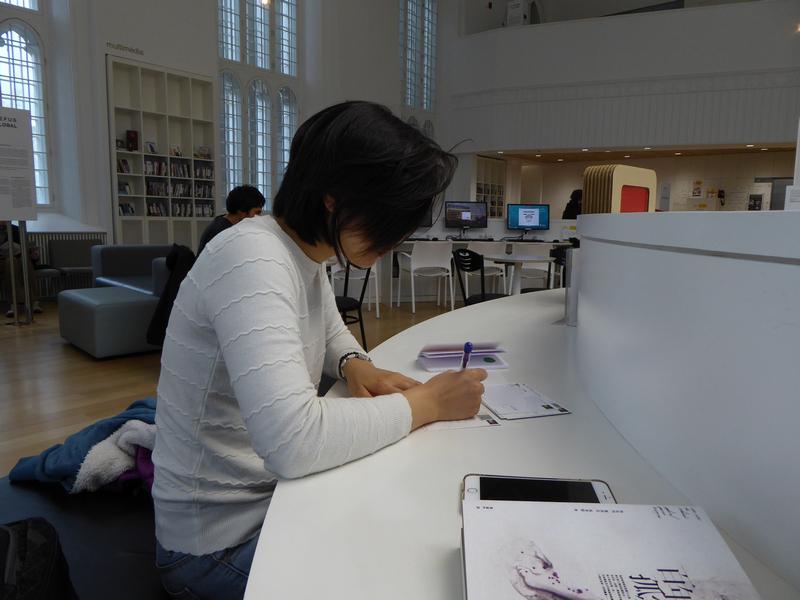 我在Institut Canadien Du Quebec坐著看書、寫著明信片